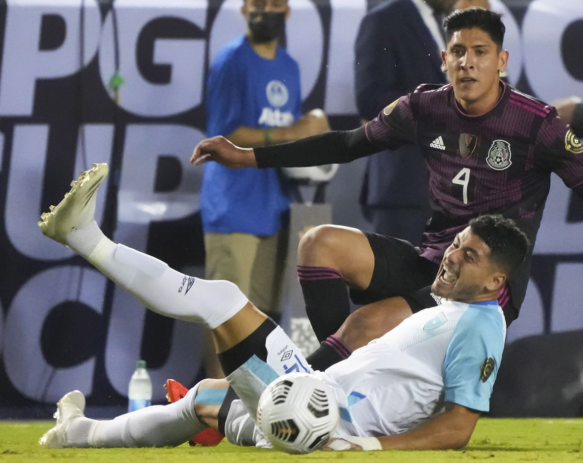 Guatemala forward Darwin Lom (14) hits the turf in front of Mexico defender Edson Álvarez (4) during the first half of a CONCACAF Gold Cup Group A soccer match at the Cotton Bowl on Wednesday, July 14, 2021, in Dallas.