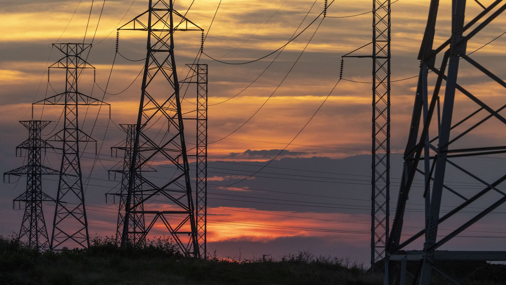 The sun sets behind electricity towers along Mountain Creek Parkway in Dallas on Wednesday, June 30, 2021. According to atmospheric scientists, record levels of ozone in the Dallas area earlier this month may be proof of a cyclical link between rising temperatures, smog and demand.