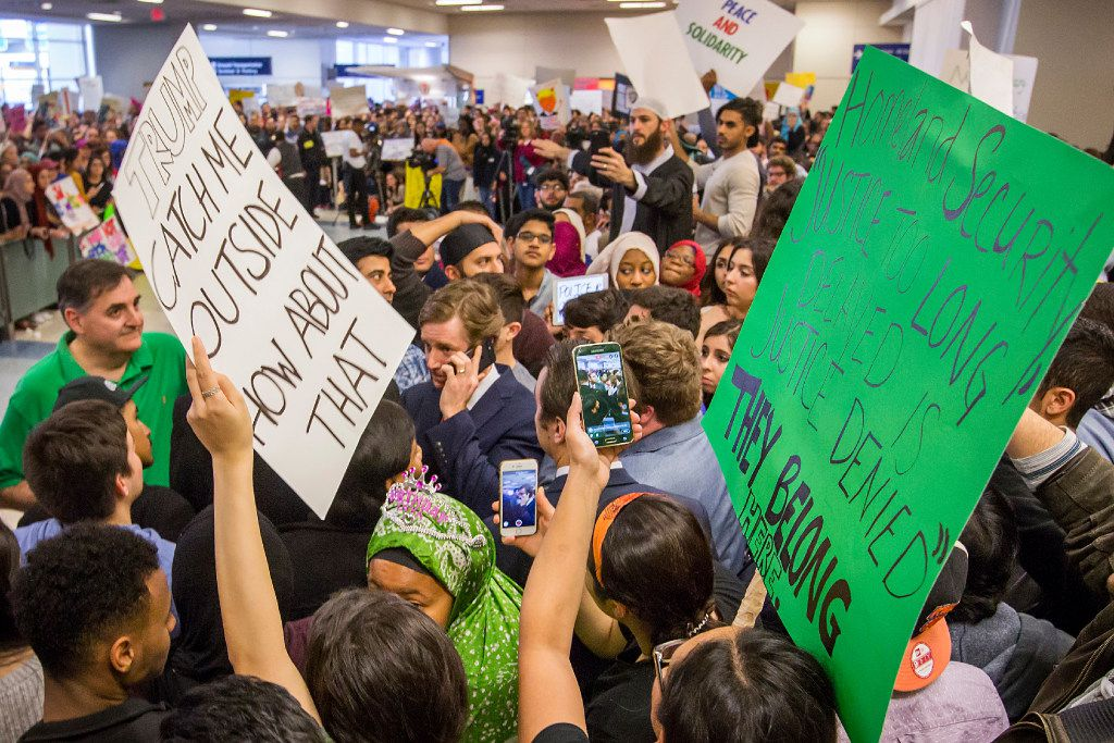 Attorney Chris Hamilton talks on his phone in a sea of protestors at DFW International Airport  on Sunday, Jan. 29, 2017.