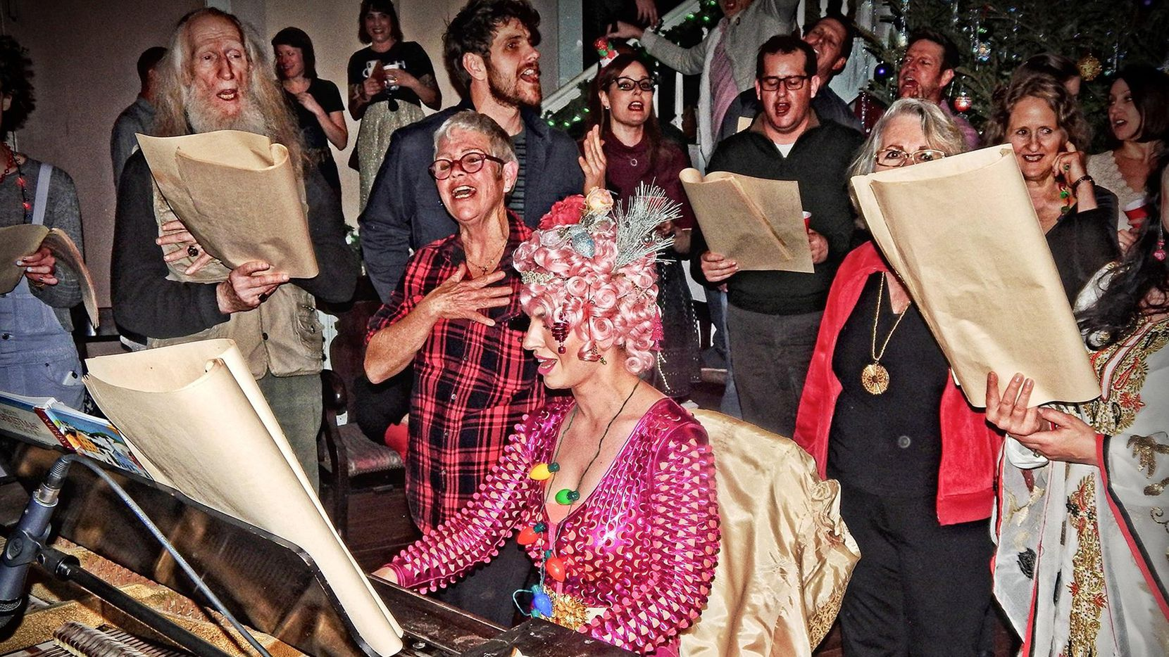 Musician and performer Poppy Xander plays the piano for a 2018 house party on Christmas Eve hosted by John Ashley Bellamy (far left with long beard) at his East Dallas home, a former Methodist Church known as the Moon Mansion. Bellamy died this month, and Poppy will now perform virtually for an online edition of the party.