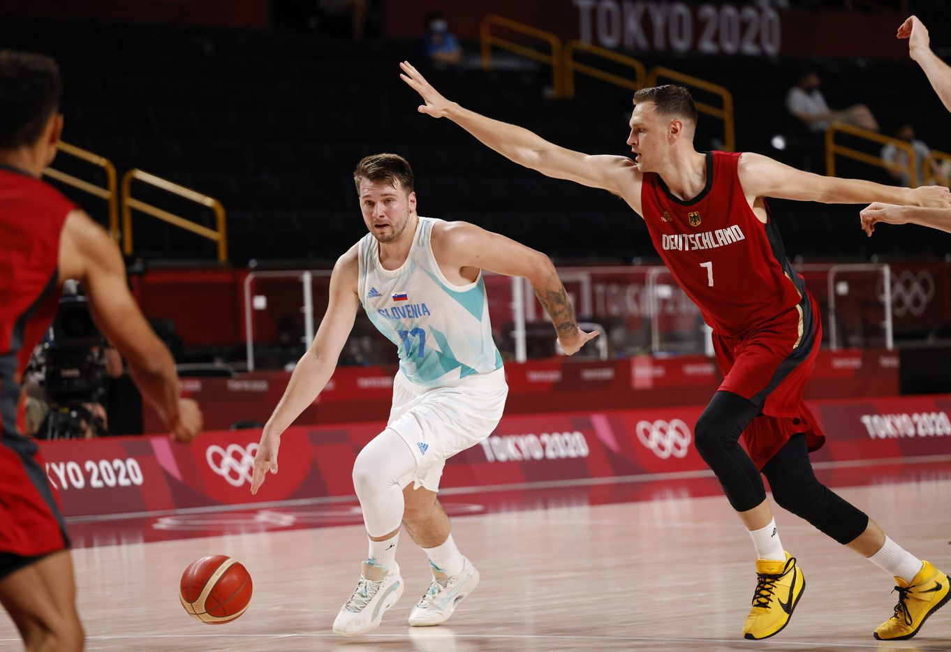 Slovenia's Luka Doncic (77) drives on Germany's Johannes Voigtmann (7) during the first half of play of a quarter final basketball game at the postponed 2020 Tokyo Olympics at Saitama Super Arena, on Tuesday, August 3, 2021, in Saitama, Japan. (Vernon Bryant/The Dallas Morning News)