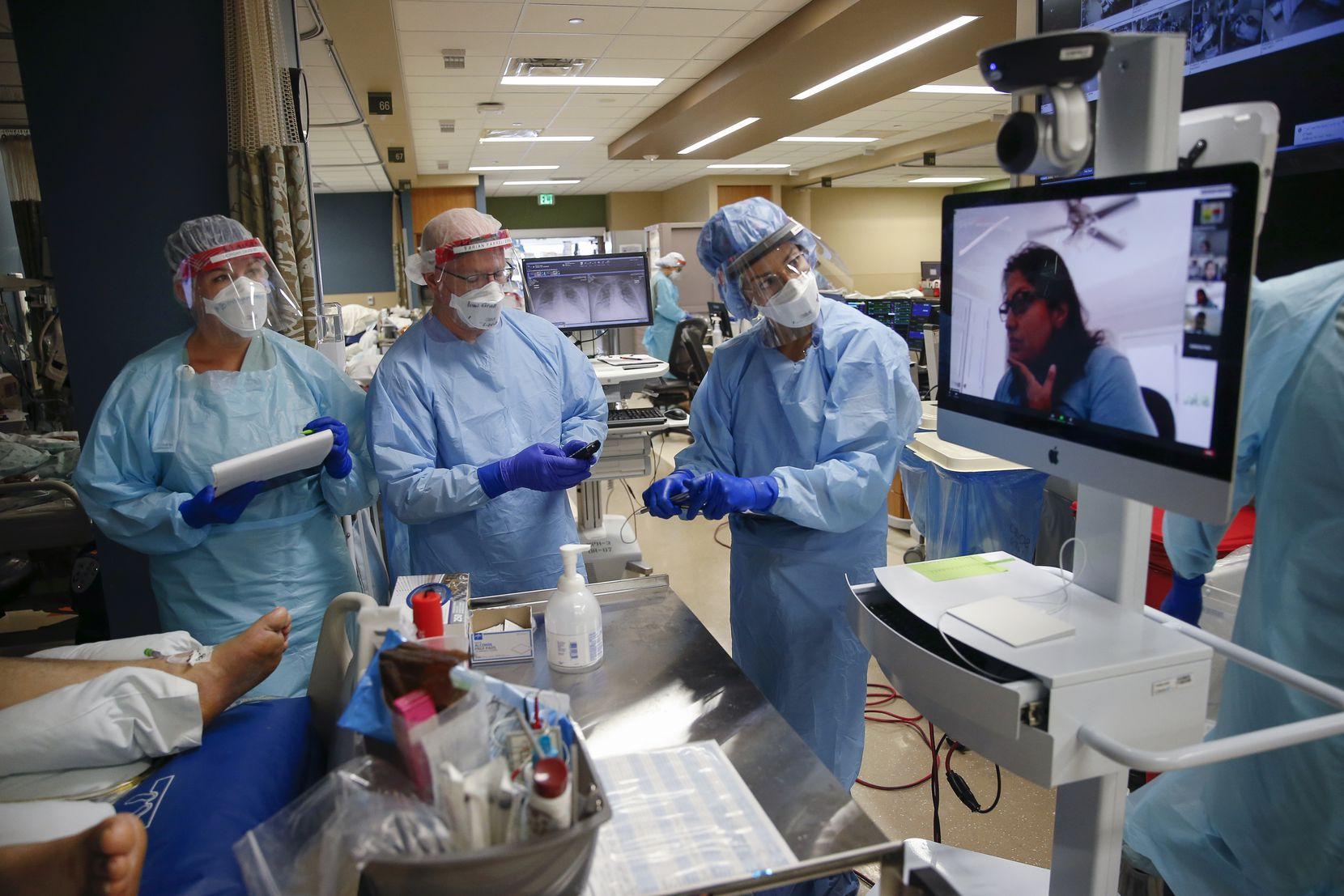 Respiratory therapist Morgan Davis (left) and Certified Registered Nurse Anesthetists Brian Farrell and Brittany O'Toole take notes as Dr. Padmaja Reddy (on-screen) virtually assists in a round of checks on coronavirus patients at Parkland Memorial Hospital.
