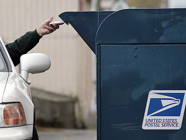 File photo of a customer dropping mail into a mailbox.