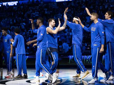 Dallas Mavericks guard Luka Dončić (77) high fives his teammates before the start of the Dallas Mavericks' home opener against the Houston Rockets on Tuesday, Oct. 26, 2021, at the American Airlines Center in Dallas.
