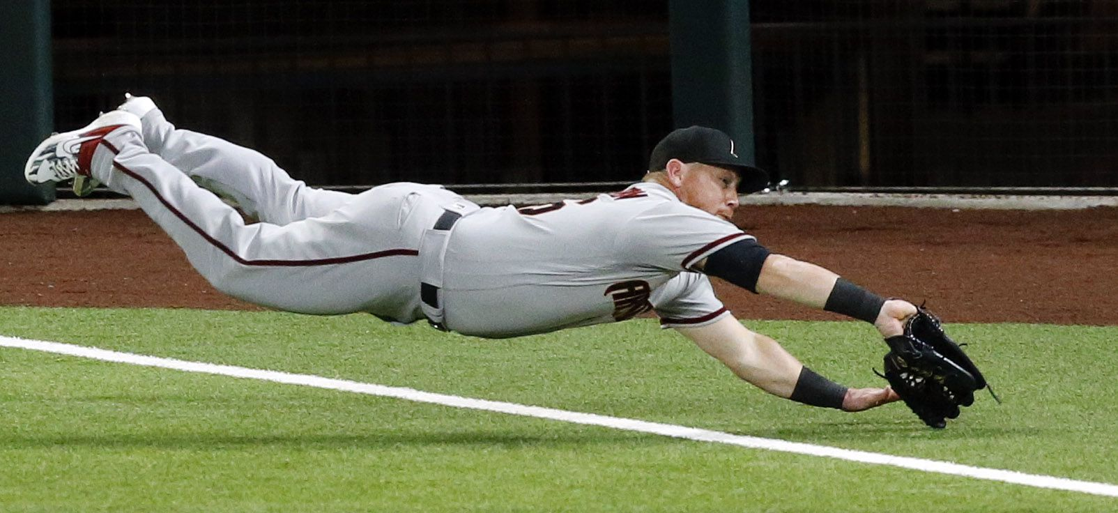 Arizona Diamondbacks right fielder Kole Calhoun (56) dives across the foul line for a pop up by Texas Rangers Elvis Andrus during the eighth inning at Globe Life Field in Arlington, Texas, Tuesday, July 28, 2020. Even though the ball was in his glove, he couldn't hang onto it. (Tom Fox/The Dallas Morning News)