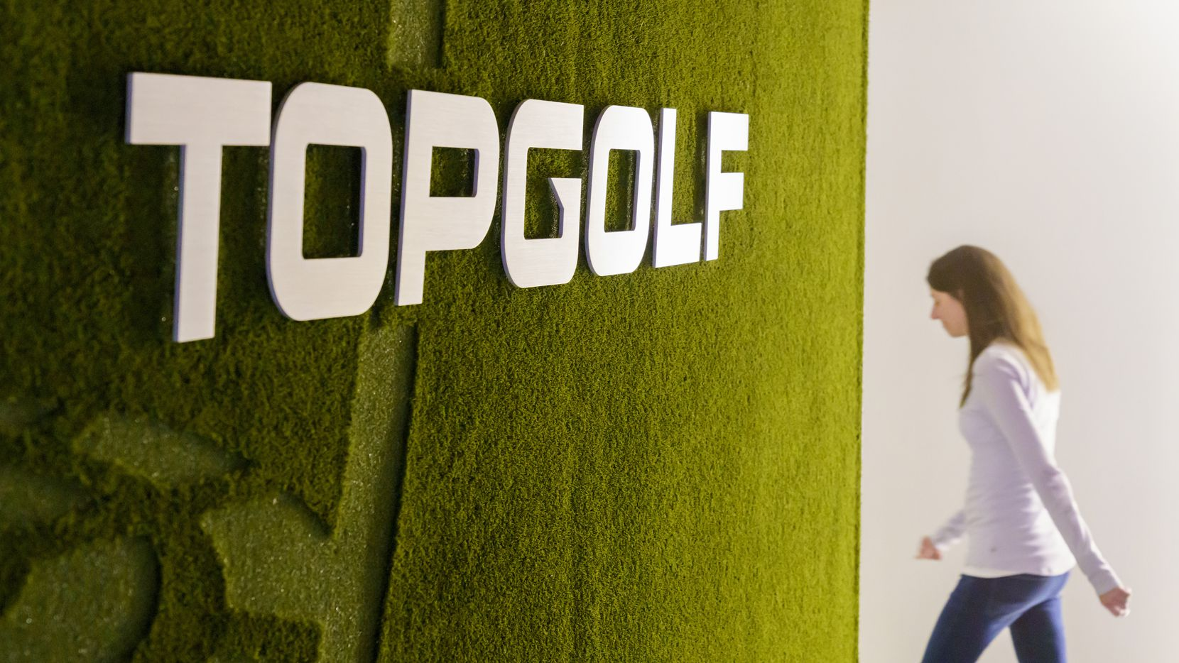 A wall covered in artificial turf and the company logo greets visitors in the lobby at Topgolf headquarters on Monday, Nov. 11, 2019, in Dallas. (Smiley N. Pool/The Dallas Morning News)