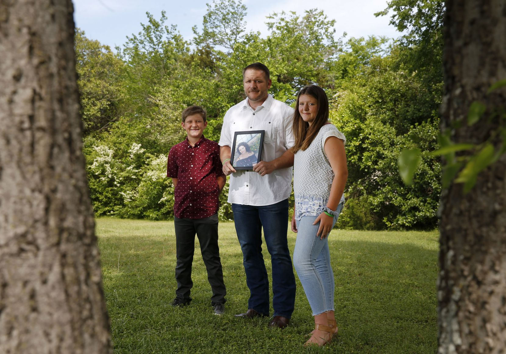 Brandon Palmer, 11, John Palmer and Bella Palmer, 13, posed for a portrait as John holds a photo of his wife, Katie Palmer, in the front yard of their home in Denison.