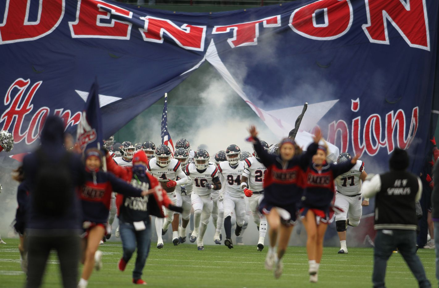Denton Ryan players storm the field as they run through their team sign prior to the opening kickoff of their game against Highland Park. The two teams played their Class 5A Division l Region ll final football playoff game at Globe Life Park in Arlington on January 1, 2021. (Steve Hamm/ Special Contributor)