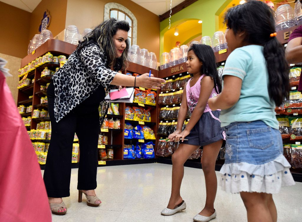 Poet and actress Priscilla Rice, 43, of Dallas speaks with Samantha Orozco (left), 6, and Heidy Cortez, 5, as before creating a poem for the kids inside El Rancho supermarket in Pleasant Grove on Aug. 26, 2017.