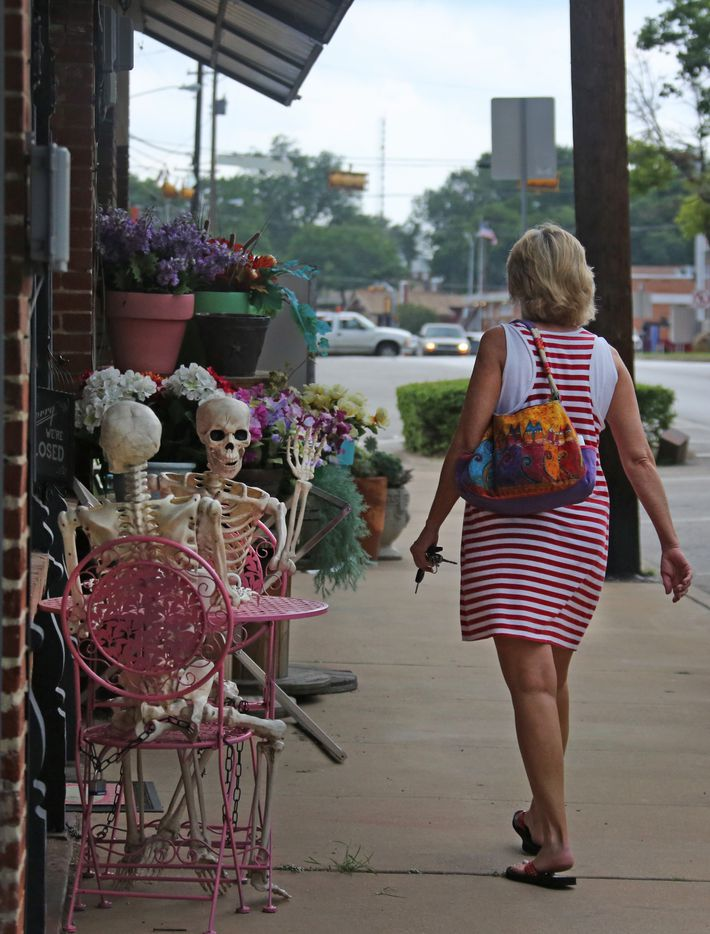 A passerby seems to get a greeting from a pair of skeletons placed at a table outside the Pieced Together Studio and Quilt Shop in Mesquite, Texas, photographed on Friday, June 2, 2017. (Louis DeLuca/The Dallas Morning News)