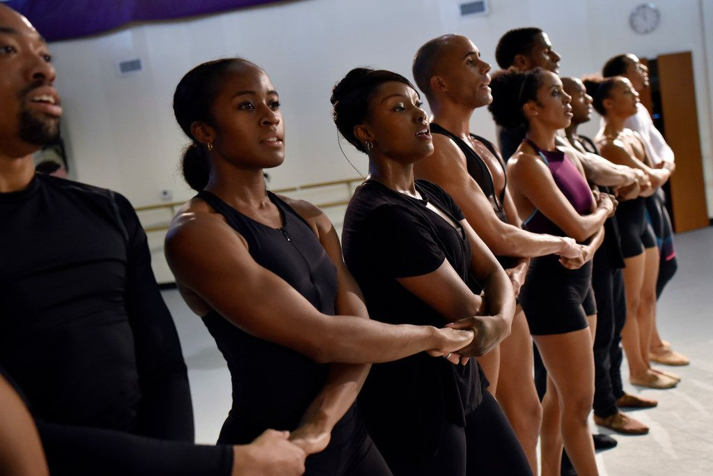Hana Delong, second from left, and Jasmine White-Killins, right, hold hands with other dancers during a rehearsal for Bodies as Site of Faith and Protest, to be performed by Dallas Black Dance Theatre on Nov. 2-4.