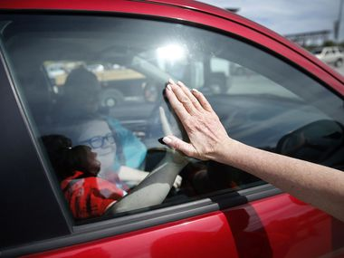 Volunteer Karen Kirk, of Houston, gives a student a high-five through the window after a drive-thru meal pickup outside AT&T Stadium in Arlington, Texas, Saturday, March 28, 2020.