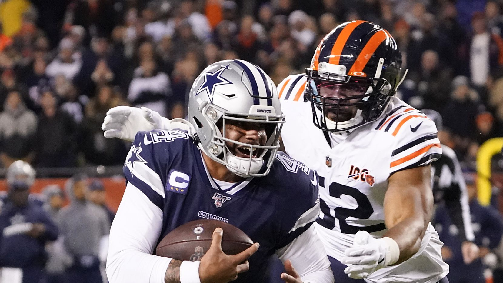 Dallas Cowboys quarterback Dak Prescott (4) is chased down by Chicago Bears outside linebacker Khalil Mack (52) during the first quarter of an NFL football game at Soldier Field on Thursday, Dec. 5, 2019, in Chicago.