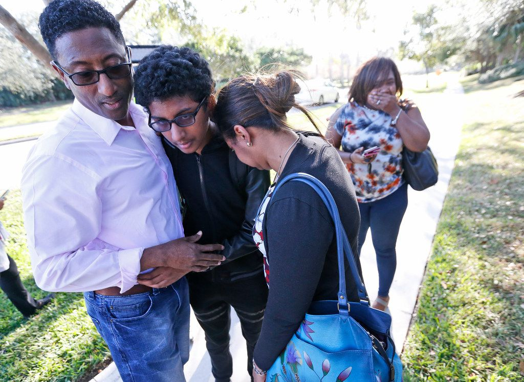 Family members embrace after a student walked out from Marjory Stoneman Douglas High School, Wednesday, Feb. 14, 2018, in Parkland, Fla. The shooting at the South Florida high school sent students rushing into the streets as SWAT team members swarmed in and locked down the building. Police were warning that the shooter was still at large even as ambulances converged on the scene and emergency workers appeared to be treating those possibly wounded. (AP Photo/Wilfredo Lee)