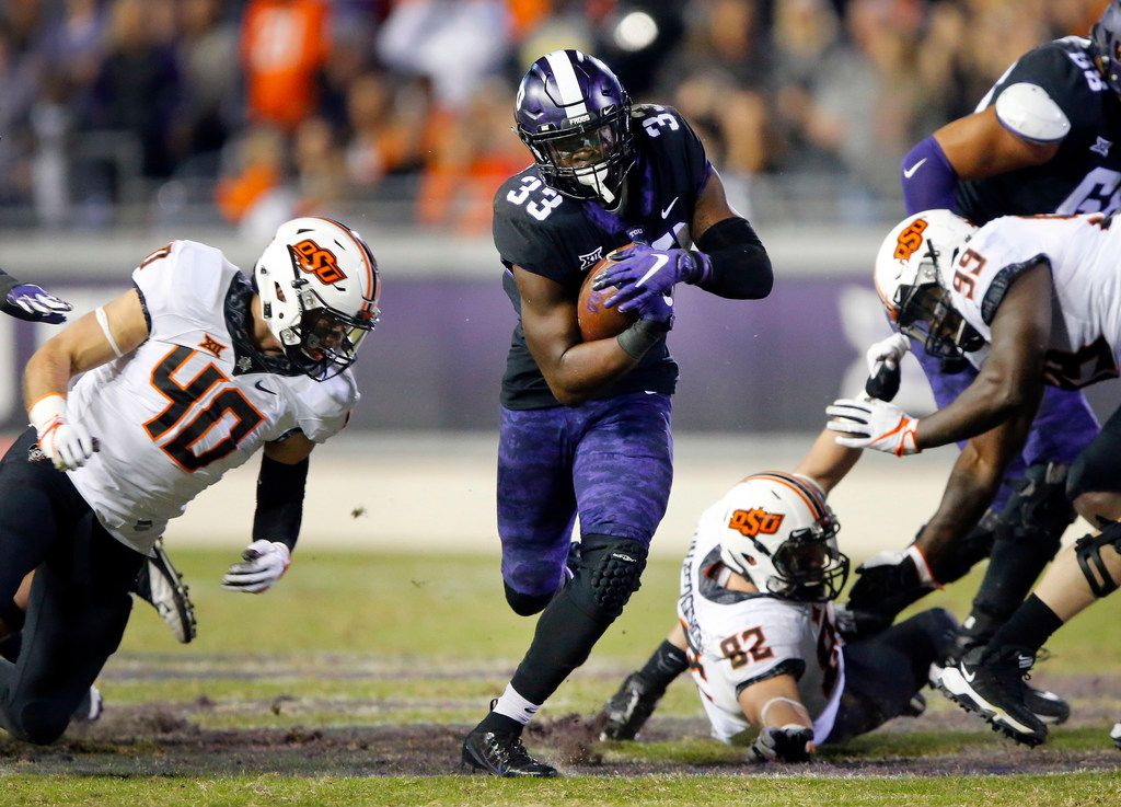 FILE - TCU Horned Frogs running back Sewo Olonilua (33) finds a hole in the Oklahoma State Cowboys defense as he rushes during the third quarter at Amon G. Carter Stadium in Fort Worth, Texas, Saturday, November 24, 2018. The Frogs hung onto win, 31-24. (Tom Fox/The Dallas Morning News)