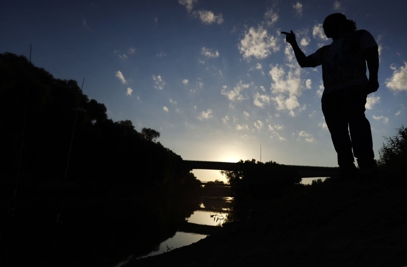Odell Allen watches his lines as he fishes for alligator gar in the Trinity River near the Westmoreland bridge, early Monday morning, August 30, 2021. (Tom Fox/The Dallas Morning News)
