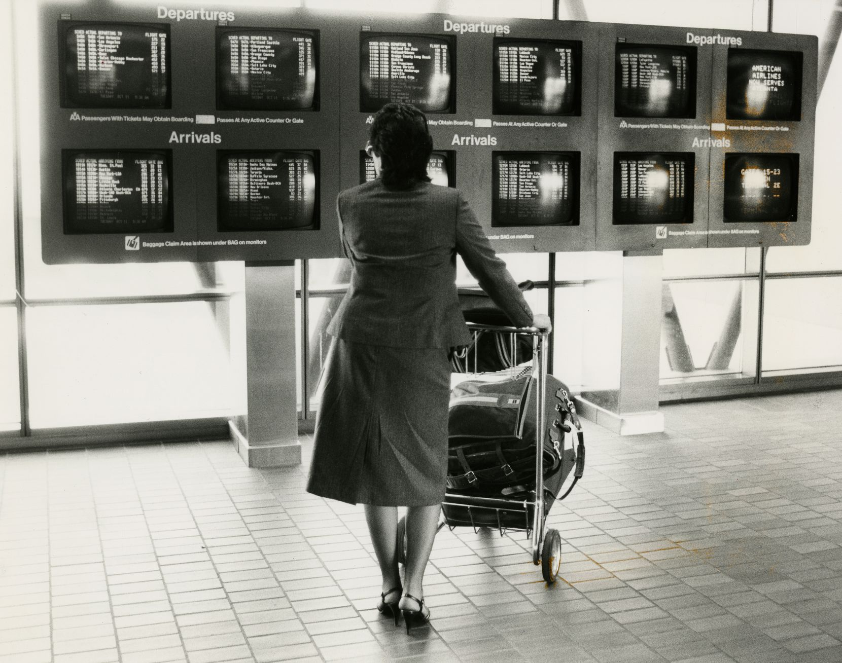 A passenger checks arrivals and departures at DFW International Airport in 1981.