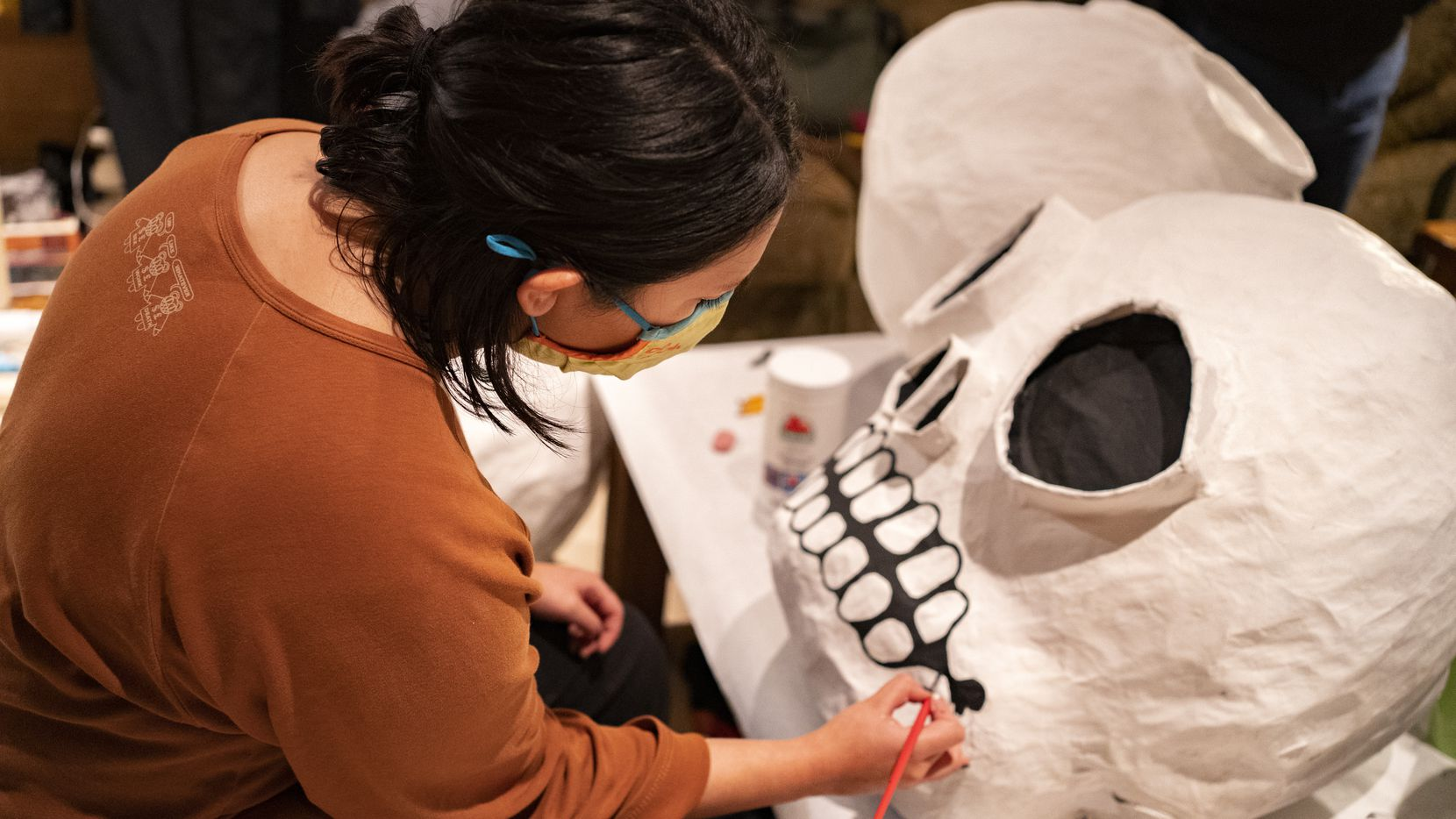 Paloma Salas works on her Day of the Dead puppet on the rainy evening of October 27, 2020 in Dallas. The puppet will be used in a public protest over the many deaths in the COVID-19 pandemic.