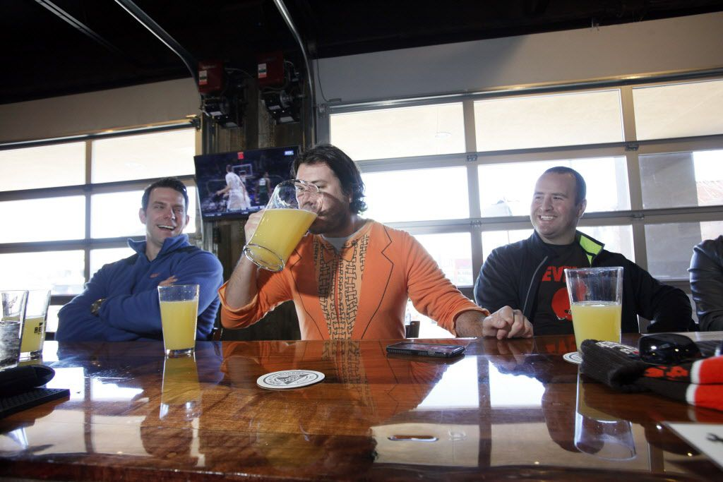 Cory Yeager, 34, left, and Chad Dean, 31, right, watch as Chaps Tucker, 30, wearing a onesie, drinks a pitcher full of mimosa while sitting at the bar with friends during brunch at 504 Bar and Grill, on Sunday, Jan. 10, 2016 on Greenville Avenue in Dallas.