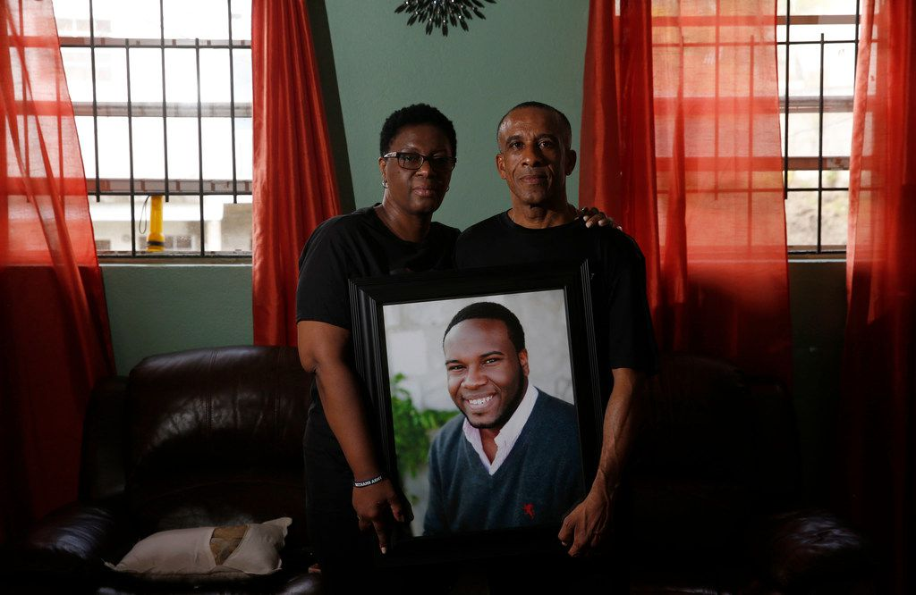 Allison and Bertrum Jean hold a photo of their son Botham Jean at their home in Castries, St. Lucia.
