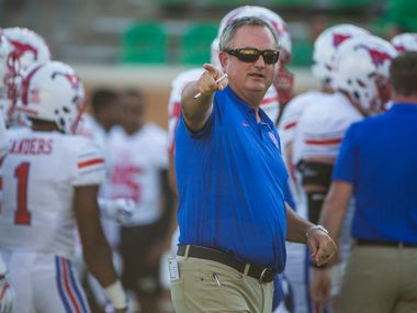 Southern Methodist Mustangs head coach Sonny Dykes works with players during warm ups prior to a game between University of North Texas and Southern Methodist University on Saturday, September 1, 2018 at Apogee Stadium in Denton, Texas.