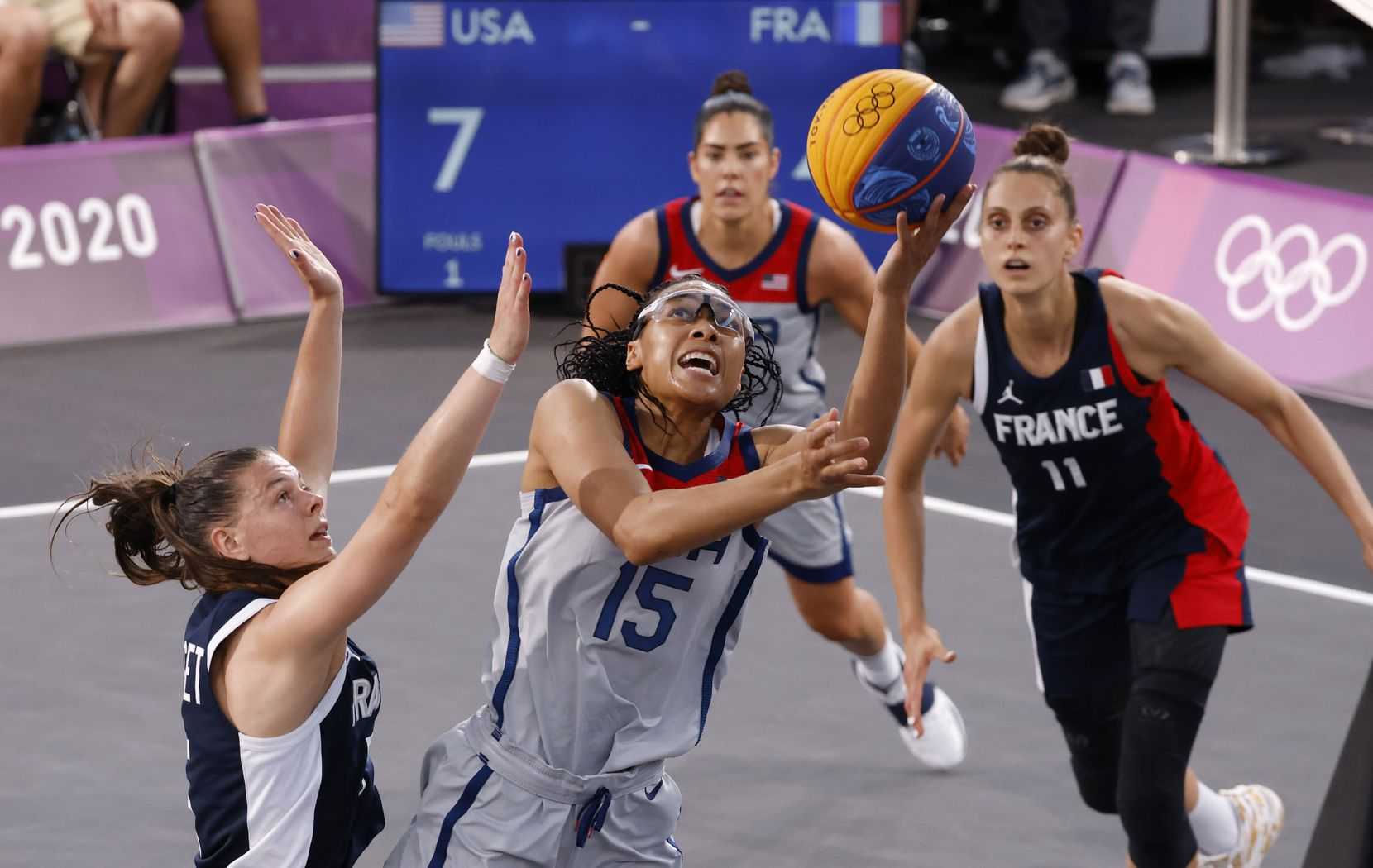 USA's Allisha Gray (15) attempts a shot in front of France's Marie-Eve Paget (5) during a 3x3 women's basketball game during the postponed 2020 Tokyo Olympics at Aomi Urban Sports Park on Saturday, July 24, 2021, in Tokyo, Japan. USA defeated France 17-10 in the game. (Vernon Bryant/The Dallas Morning News)