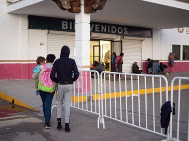 In February, migrants at the state-run migrant shelter walk into the shelter in Cd. Juarez, Chihuahua.
