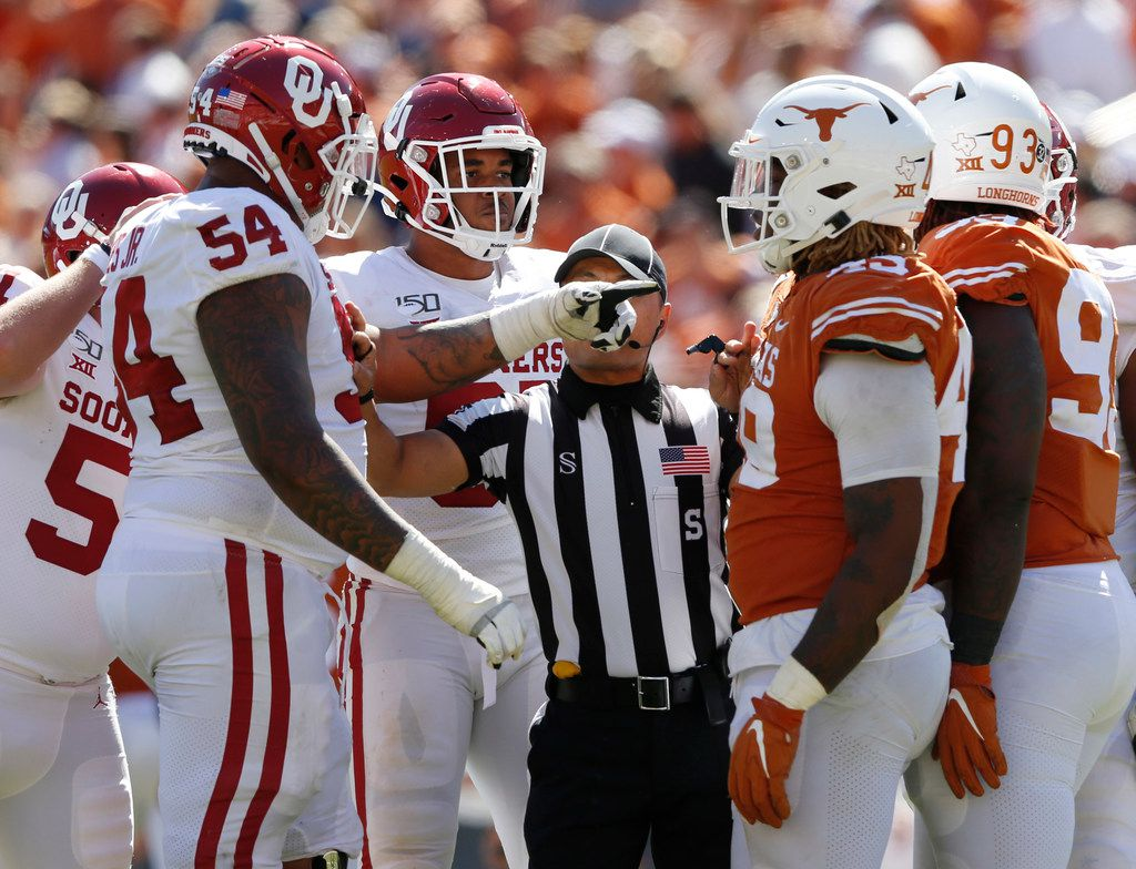 Oklahoma Sooners offensive lineman Marquis Hayes (54) and Texas Longhorns defensive lineman Ta'Quon Graham (49) are split apart by an official during the second half of play in the Red River Showdown at the Cotton Bowl in Dallas on Saturday, October 12, 2019. Oklahoma Sooners defeated Texas Longhorns 34-27.
