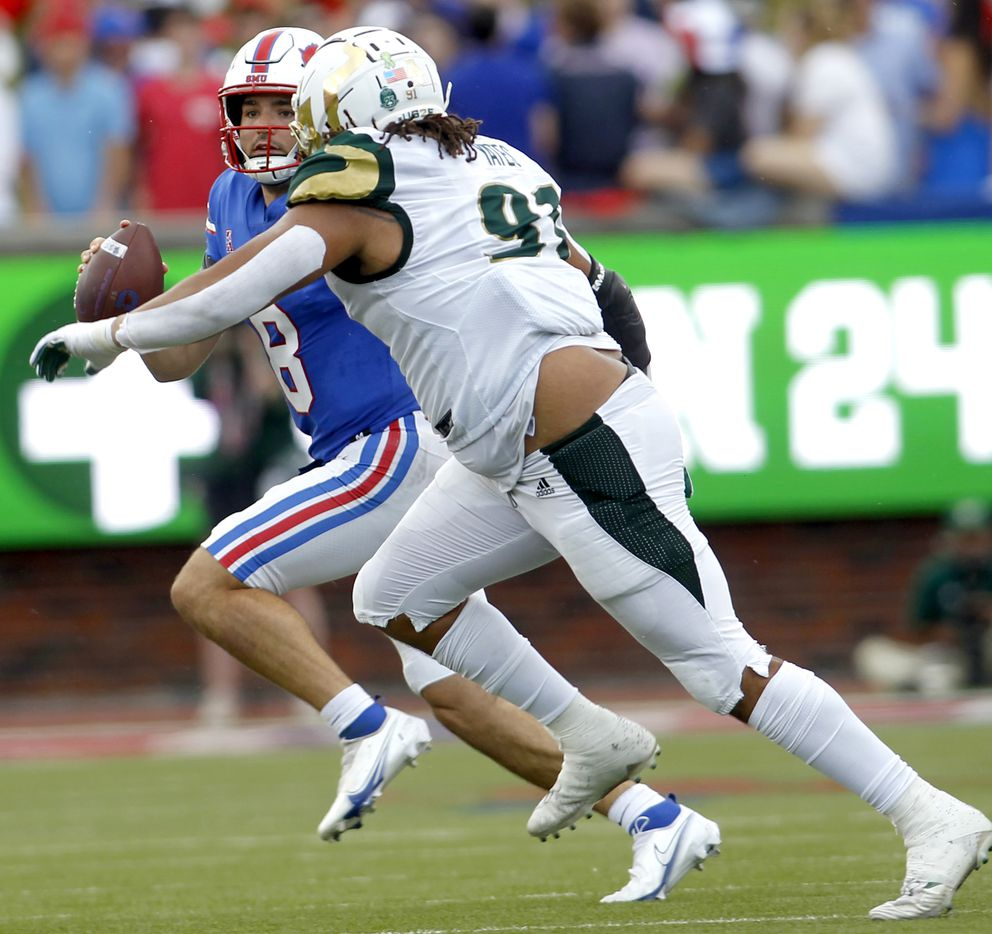 SMU quarterback Tanner Mordecai (8) rolls out to avoid the pursuit of South Florida defensive end Rashawn Yates (91) during first half action. The two teams played their NCAA football game at SMU's Ford Stadium in Dallas on October 2, 2021. (Steve Hamm/ Special Contributor)