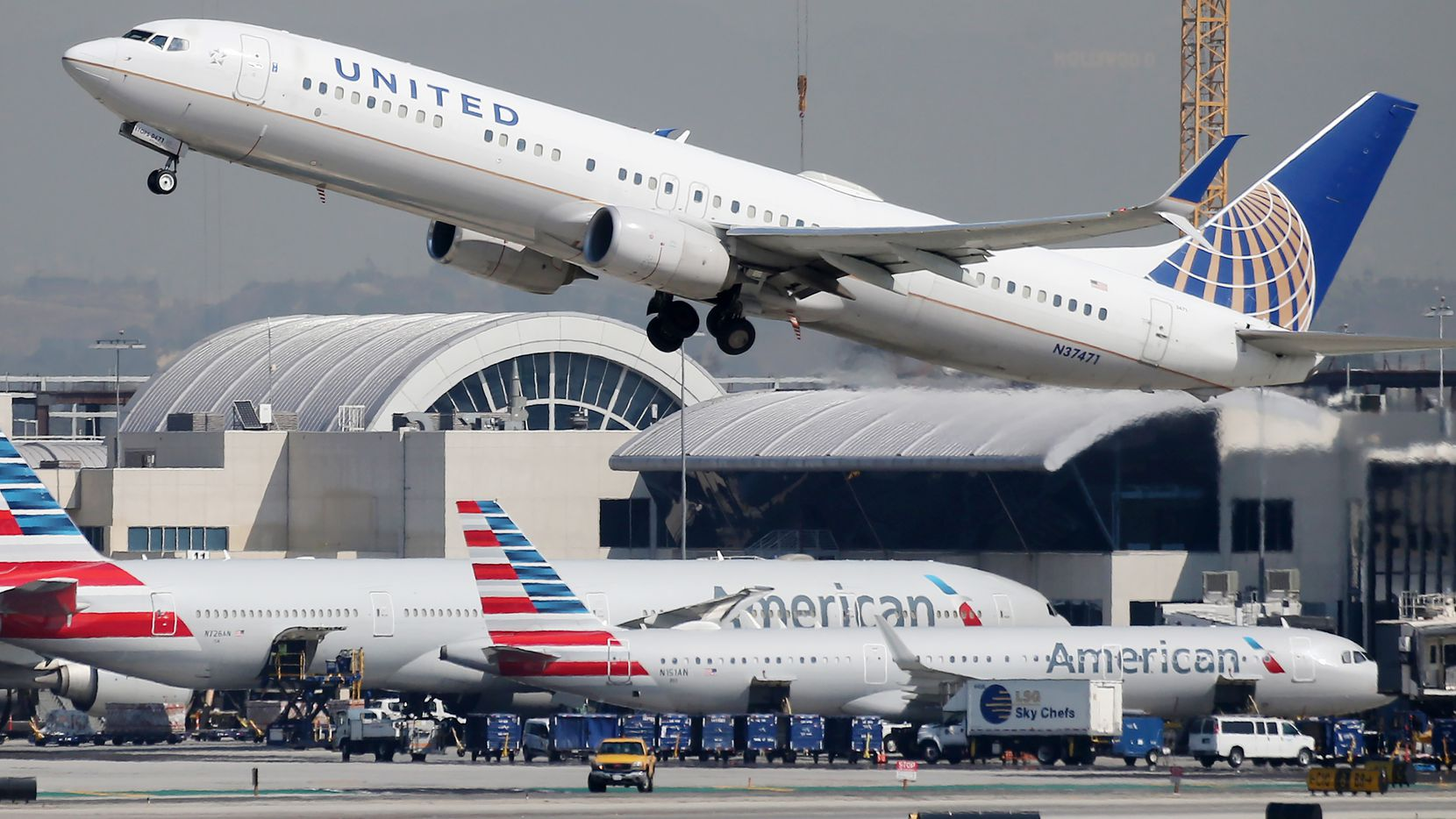 A United Airlines plane takes off above American Airlines planes on the tarmac at Los Angeles International Airport on Oct. 1.