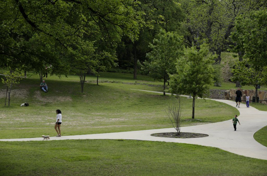 People walk around Reverchon Park  in Dallas.