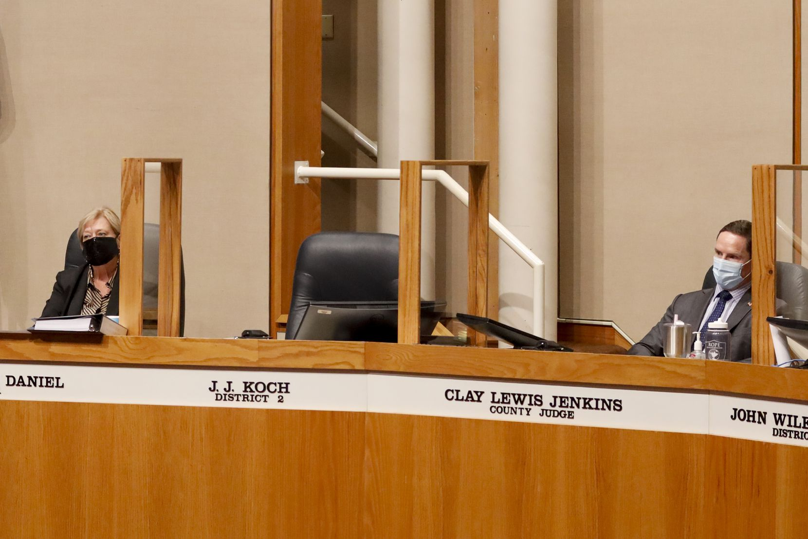 Dallas County Judge Clay Jenkins (right) and County Commissioner Theresa Daniel sit next to the empty chair of County Commissioner J.J. Koch during a Dallas County Commissioners Court meeting on Tuesday, Aug. 3, 2021, in Dallas. Koch was escorted from the meeting for refusing to wear a mask. (Elias Valverde II/The Dallas Morning News)