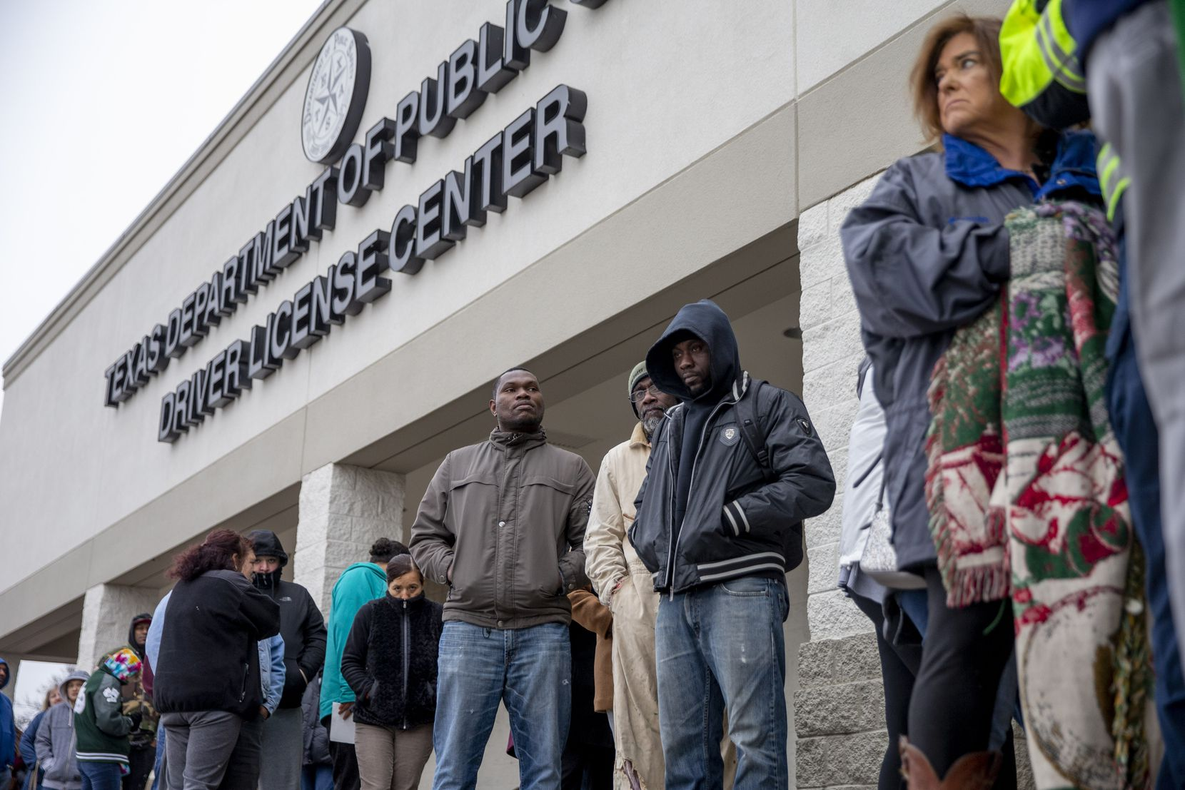 People line up at outside of the entrance at the Texas Department of Public Safety Driver License in Garland, Texas on Friday, March 1, 2019.