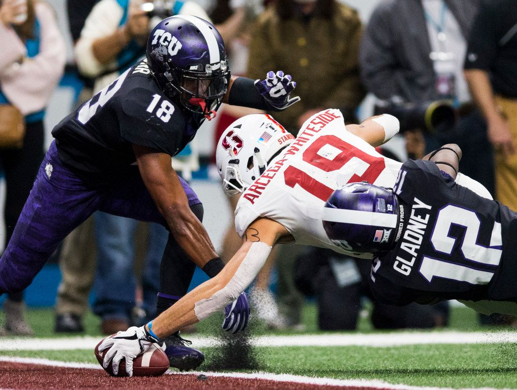 TCU Horned Frogs safety Nick Orr (18) and cornerback Jeff Gladney (12) tackle Stanford Cardinal wide receiver JJ Arcega-Whiteside (19) as he crosses the goal line for a touchdown during the second quarter of the Valero Alamo Bowl between TCU and Stanford on Thursday, December 28, 2017 at the Alamodome in San Antonio. (Ashley Landis/The Dallas Morning News)