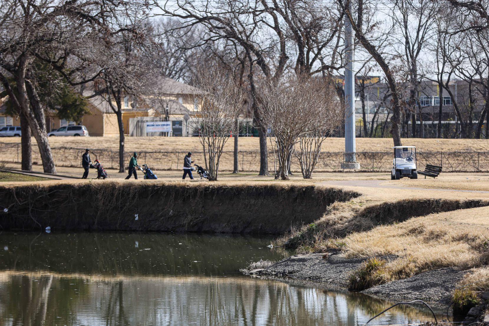 Golfers walk near an eroded section of Tenison Glen Golf Course in Dallas.