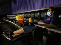 "Ben Levy of Plano watches trailers play as he waits for ""Sonic the Hedgehog,"" to start at Cinemark West in Plano, on Friday, June 19, 2020. After being closed for months due to the coronavirus pandemic, the theater reopened today."