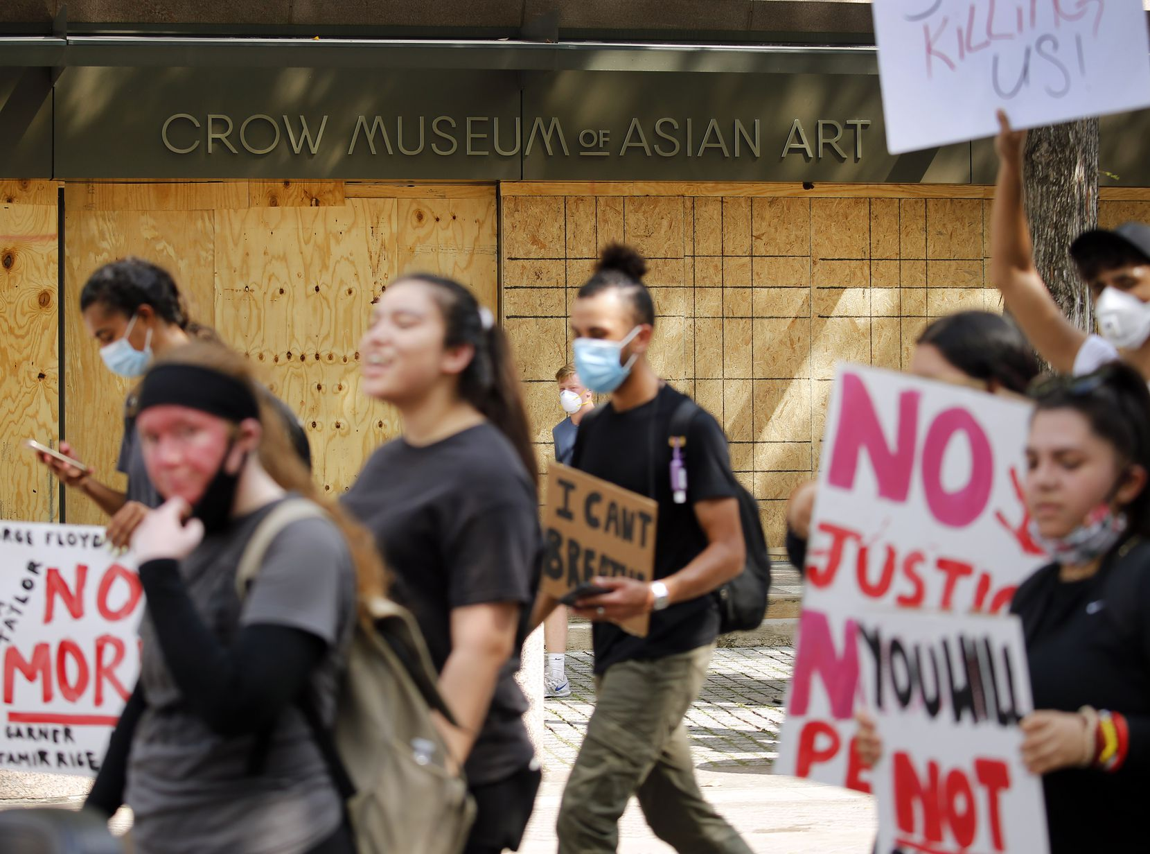 Protestors supporting Black Lives Matters march past the boarded up Crow Museum of Asian Art in the Arts District of downtown Dallas, Tuesday, June 2, 2020.