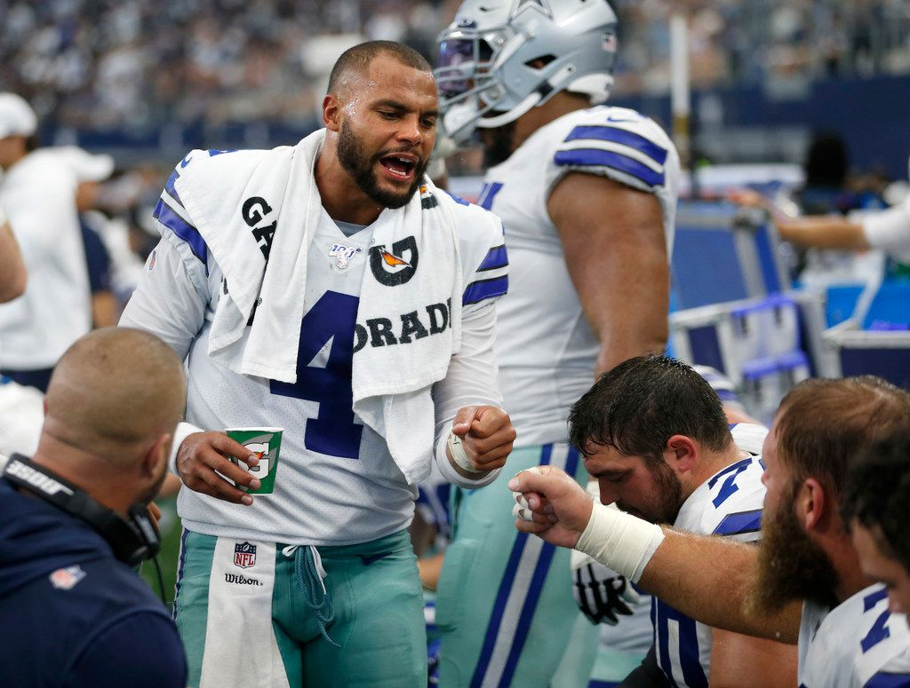 Dallas Cowboys quarterback Dak Prescott (4) celebrates with Dallas Cowboys center Travis Frederick (72) and the rest of the offensive line after scoring a touchdown during the first half of play in the home opener between the Dallas Cowboys and New York Giants at AT&T Stadium in Arlington, Texas on Sunday, September 8, 2019.