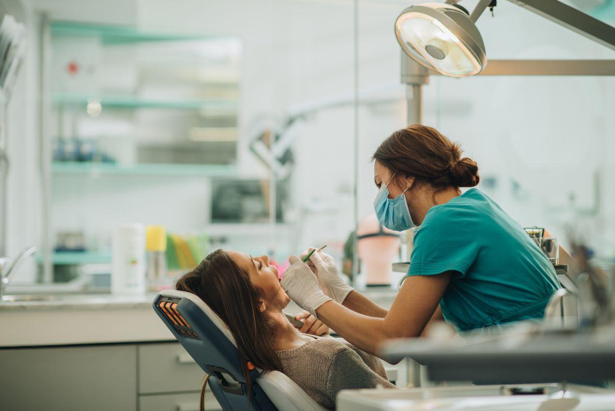 Una mujer recibe atención a su dentadura en un consultorio dental.