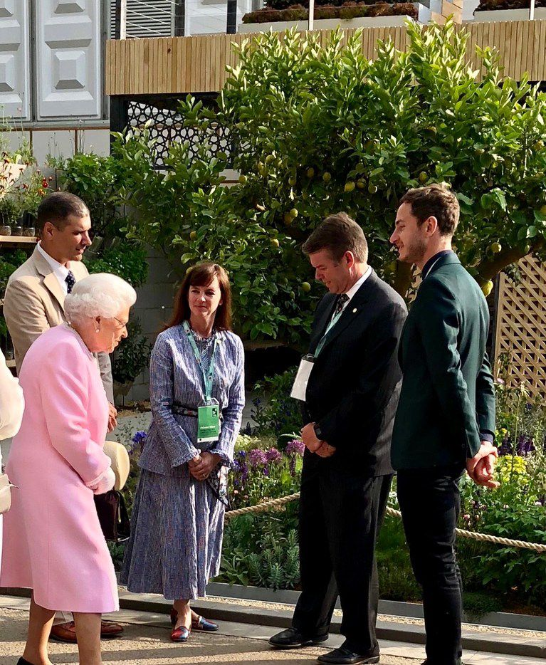 Queen Elizabeth meets Alfonso Montiel, director of business strategy and development for Lemon Tree Trust, left, Stephanie and Hunter Hunt and Tom Massey, who designed the Lemon Tree Trust Garden at the Chelsea Flower Show on May 18. The nonprofit entry won a Silver Gilt Medal. (Stephanie Hunt)