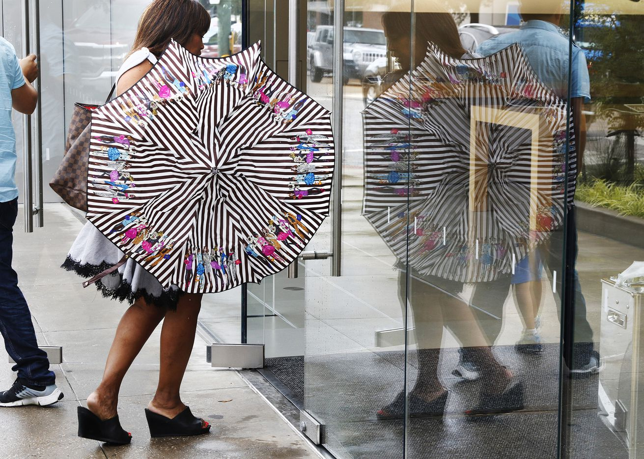 Veronica Lewis of Dallas finds shelter from a quick downpour at the Apple store on Knox St. in Dallas on Friday, June 2, 2017.