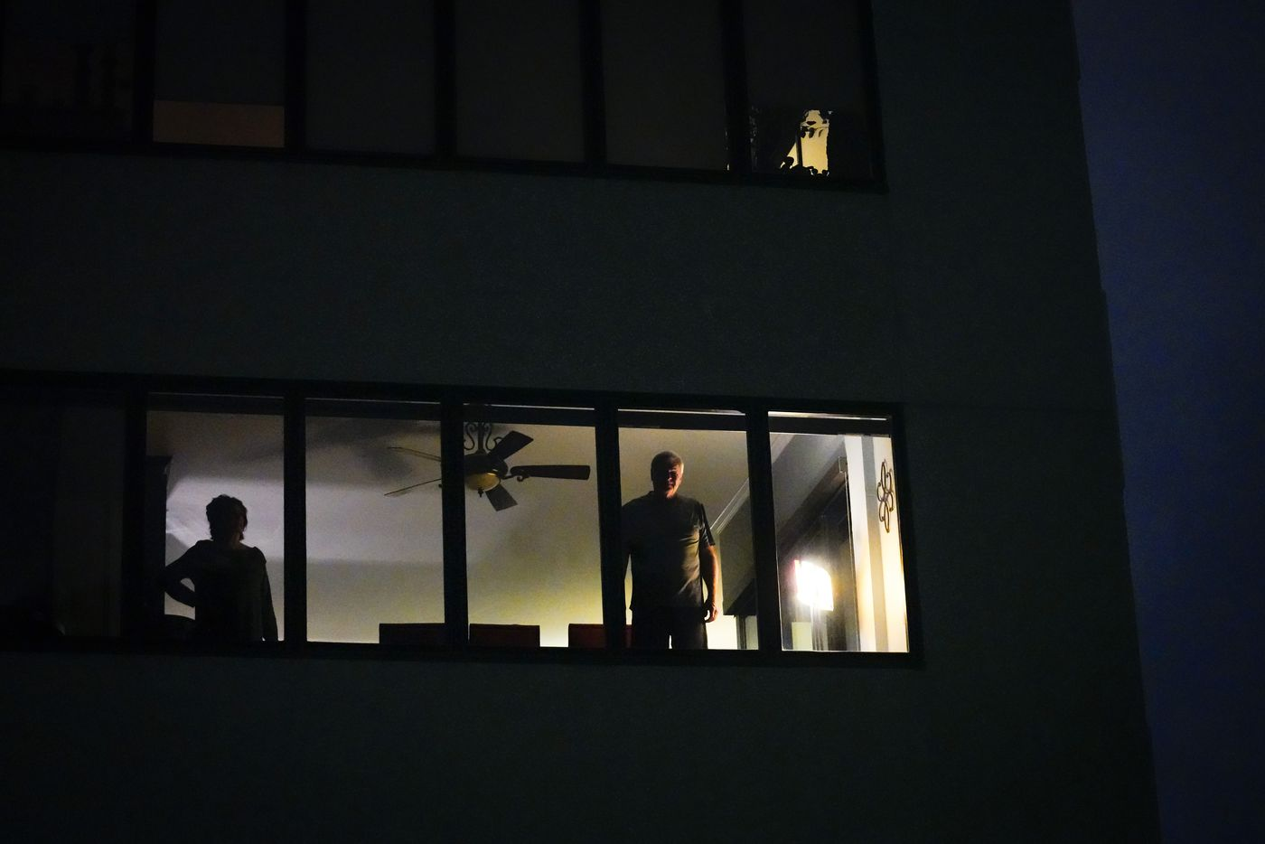 People watch from a high rise window at La Tour Condominiums as demonstrators march through Uptown after a Kentucky grand jury brought no charges against Louisville police for the killing of Breonna Taylor on Wednesday, Sept. 23, 2020.