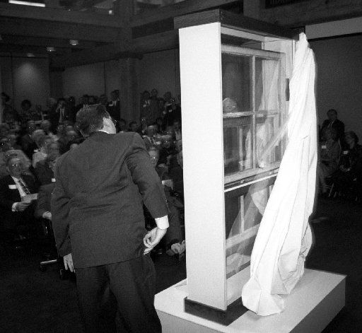 """Jeff West and Caruth Byrd, barely visible through the window, unveil the Sniper's Perch  window from the sixth floor that was removed six weeks after the  shooting. The window was one of two """"missing pieces of history"""" that were added to the Sixth Floor Museum during a ceremony and reception in 1997."""