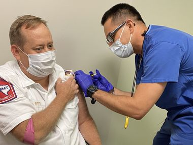 Hospitals often require workers to get a vaccine against the flu and other diseases, but such requirements are not common among private firms. Here, Allen Fire Chief Jonathan Boyd volunteers for a COVID-19 vaccine study.