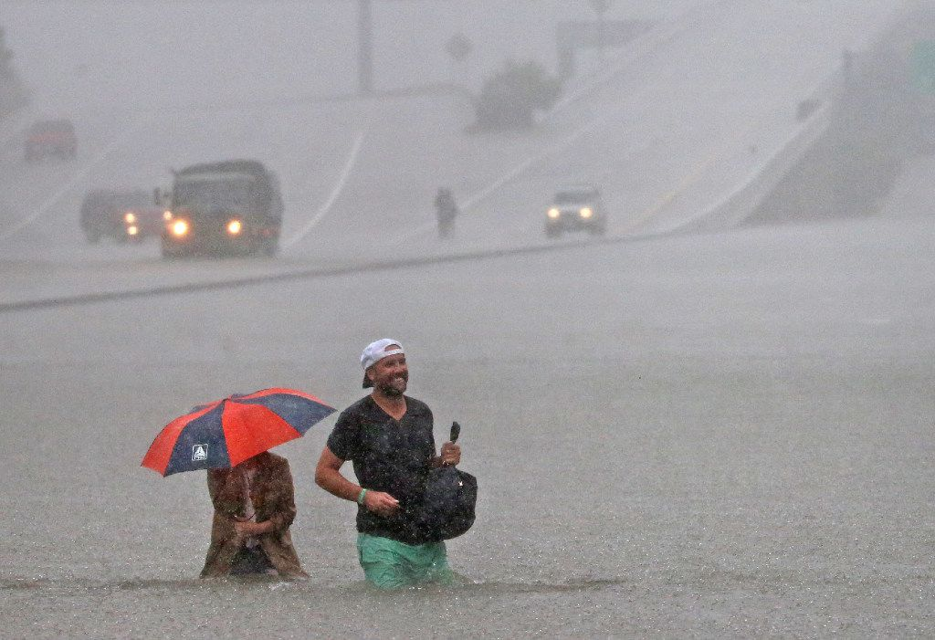 Motorists stranded in the flooding on  Interstate 610 south in Houston make their way to higher ground in the flood waters. (Louis DeLuca/The Dallas Morning News)