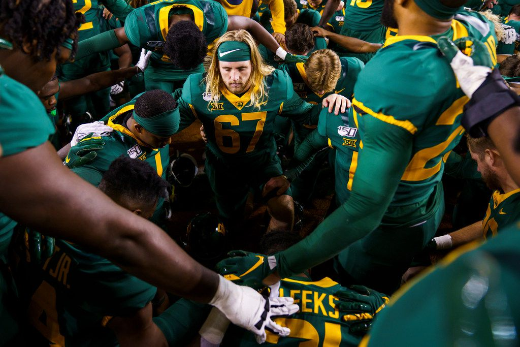 Baylor player, including long snapper Thor Rodoni (67) kneel in prayer after a victory over West Virginia in an NCAA football game at McLane Stadium on Thursday, Oct. 31, 2019, in Waco, Texas.