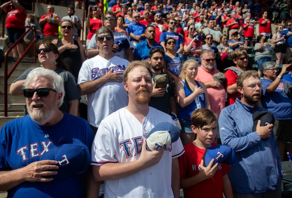 From left, Ken McClelland, his son Kevin McClelland, his grandson Avery McClelland, 11, and his other son Matt McClelland stand for the National Anthem during the Rangers' final game ever played at Globe Life Park in Arlington, Texas, on Sunday, Sep. 29, 2019. Following the game, fans enjoyed a ceremony and parade to place home plate at the new, adjacent Globe Life Field.