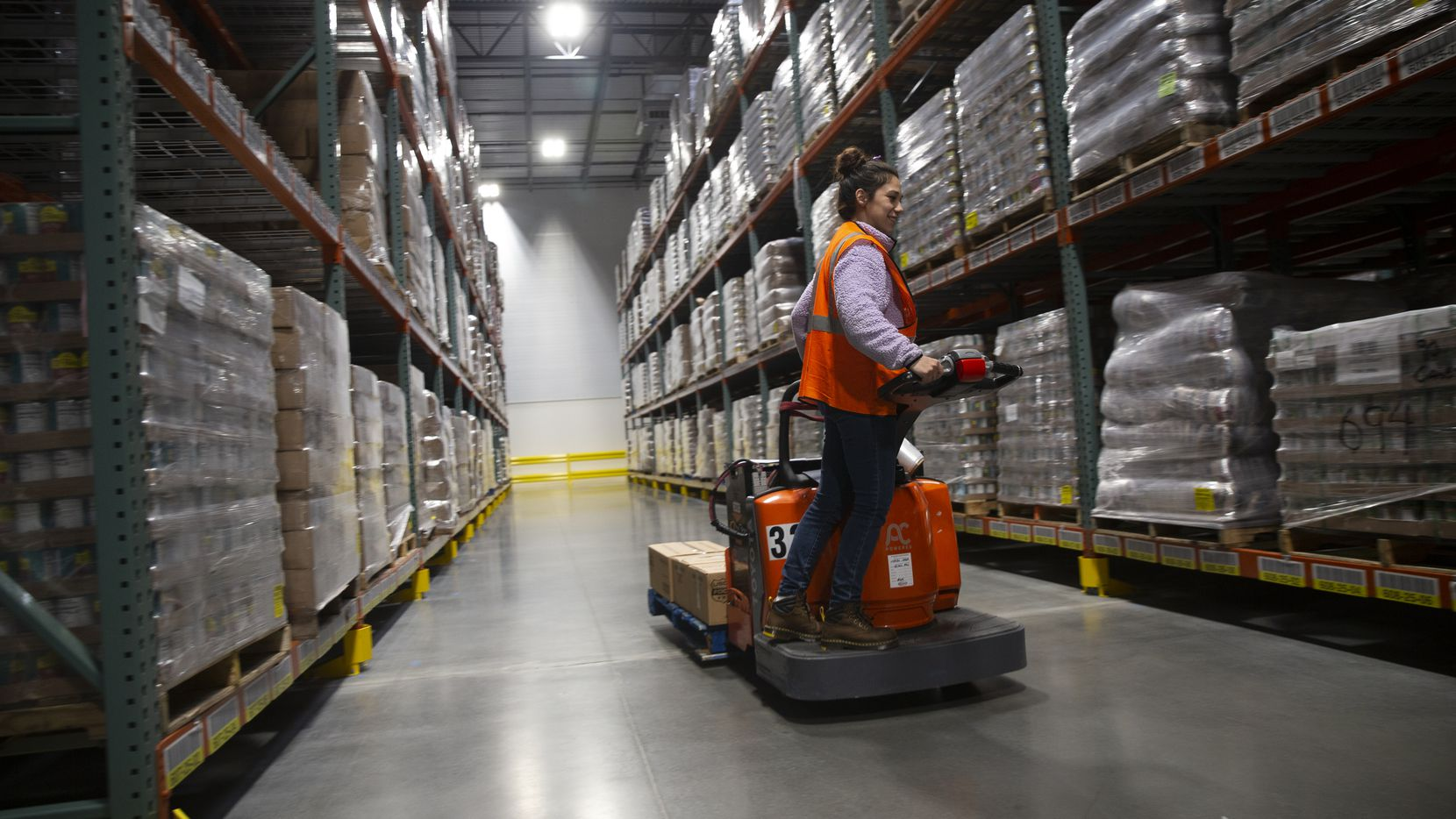 Veronica Gonzalez, a distribution associate for the North Texas Food Bank, works on a delivery in the USDA food room on Feb. 6, 2020 in Plano. The North Texas Food Bank has gotten millions of extra pounds of food from the federal government due to purchases by the Trump administration in the wake of trade conflict with China.