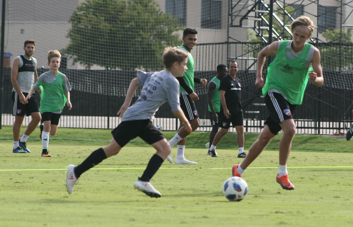 Thomas Roberts (foreground in green) plays defense against one of the two FC Dallas summer camp kids who got to join the training session. The other summer camper is in green in the background.