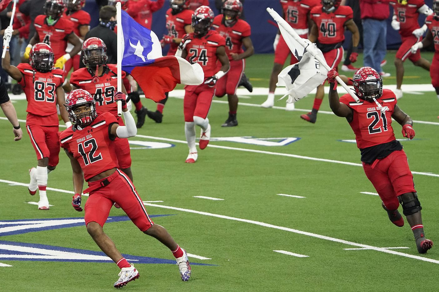 Cedar Hill's Brian Rainey (12) and Kris Allen (21) carry flags as they lead their team on to the field to face Katy in Class 6A Division II state football championship  game at AT&T Stadium on Saturday, Jan. 16, 2021, in Arlington, Texas.